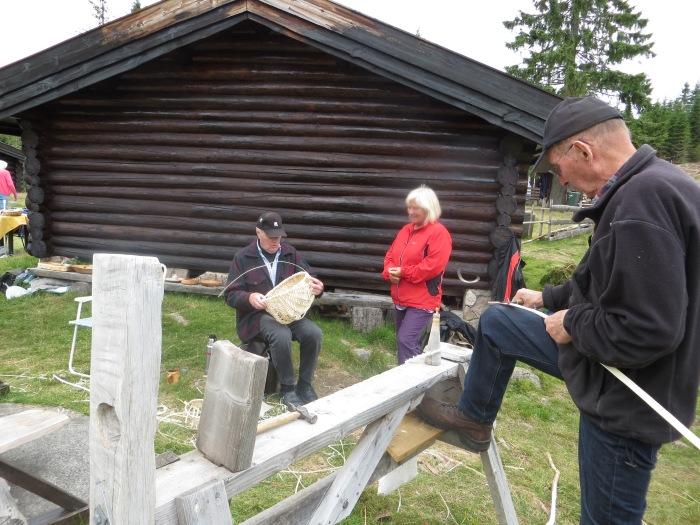 Hans Røsholt og Reidar Røse viser flisefatfletting. Toril Engelbretsen ser på. 21.7.12